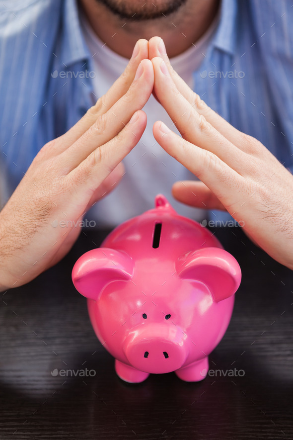 Casual man sheltering piggy bank in the living room Stock Photo by ...