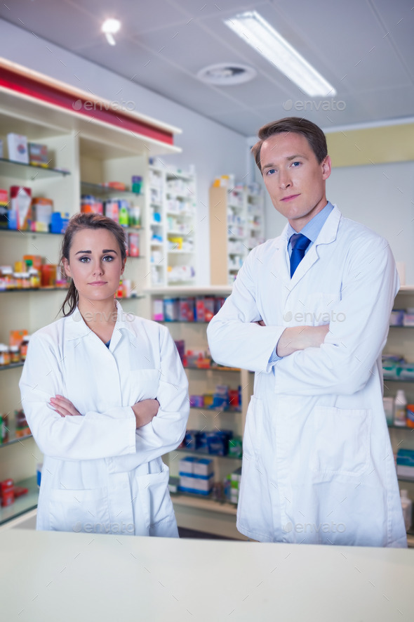 Pharmacist and his trainee standing with arms crossed in the ...