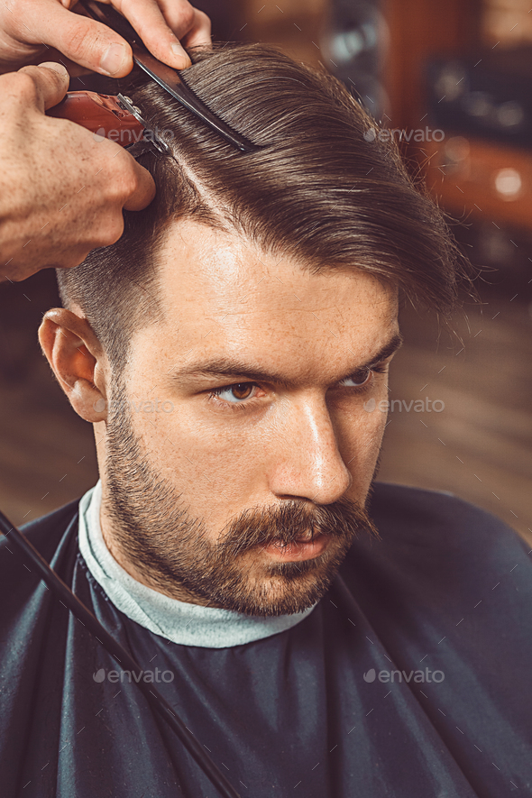 The Hands Of Young Barber Making Haircut To Attractive Man In