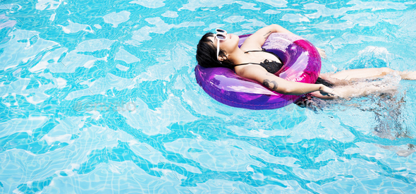 Asian Woman Floating In The Swimming Pool With Inflatable Tube