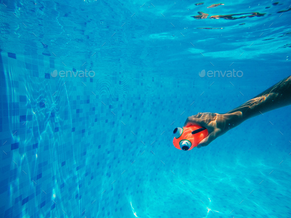 Child playing with generic rubber fish toy in swimming for Fake fish that swim