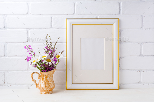 Gold decorated frame mockup with chamomile and purple flowers in ...