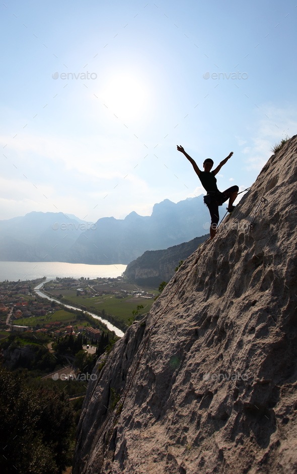 silhouette of a female rock climber with outstretched arms stock