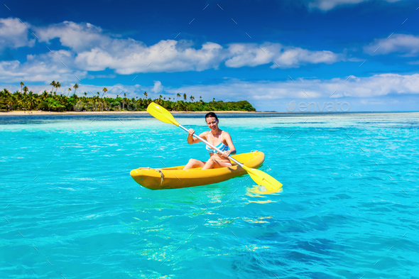woman kayaking in the ocean on vacation in tropical island stock