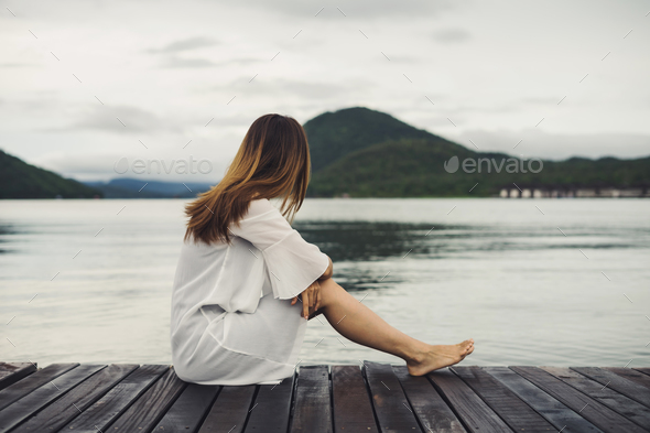 Lonely woman sitting on wooden pier and looking at the lake Stock Photo by kitzstocker