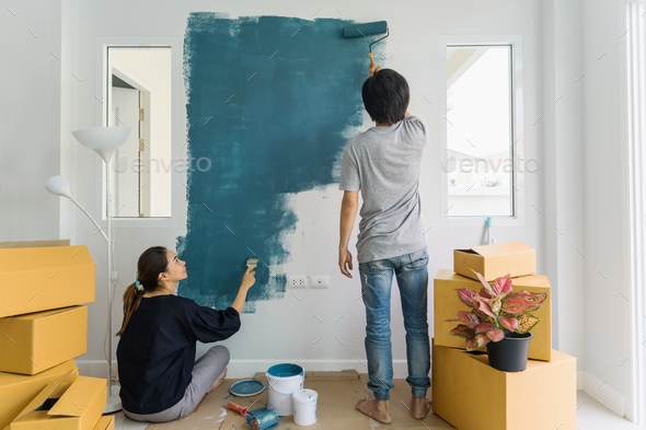 Superb Young Asian Couple Painting Interior Wall With Paint Roller In New House    Stock Photo