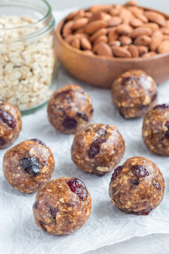 Healthy homemade energy balls with cranberries, nuts, dates and rolled oats on parchment, vertical Stock Photo by iuliia_n