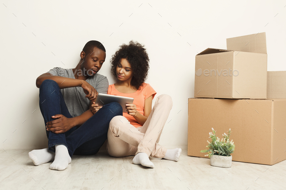 African-american sitting on floor at new appartment Stock Photo by Milkosx