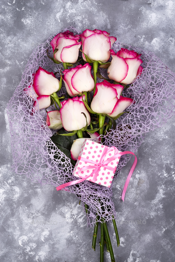 Red white rose flower bouquet with pink gift box on stone table ...