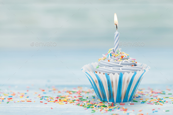 sweet cupcake with candle stock photo by karandaev