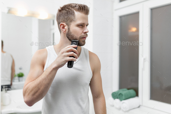handsome bearded man trimming his beard with a trimmer stock photo
