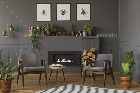 Wooden Table Between Grey Armchairs In Retro Flat Interior With Stock Photo  By Bialasiewicz
