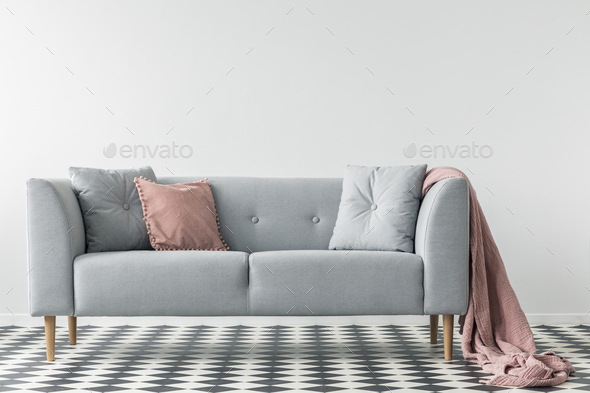 Pink Blanket On Grey Couch With Pillows On Checkered Floor In Wh   Stock  Photo