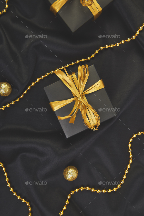luxury black gift boxes with gold ribbon stock photo by bondarillia