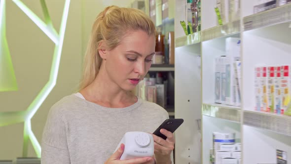 Female Using Smart Phone, Browsing Information Online While Shopping Medication