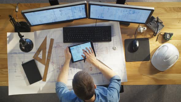 top view of architectural engineer draws on his blueprints