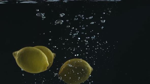 Three Juicy Lemons Dipping in Water, Lemonade Ingredient, Refreshment, Vitamin C