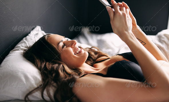 Beautiful young woman in underwear reading sms on bed - Stock Photo - Images