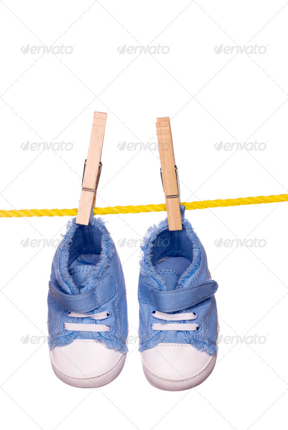 Baby shoes hanging on a clothesline - Stock Photo - Images