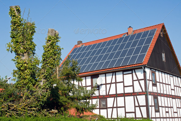 Old frame house with solar cells on the roof - Stock Photo - Images