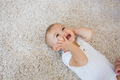 High angle view of a happy cute baby lying on carpet at home