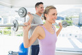 happy fit woman and man lifting barbells in the exercise room