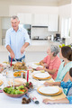 Senior man serving meal to family at dining table - PhotoDune Item for Sale