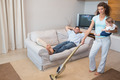 Full length portrait of woman cleaning house while carrying baby with man relaxing on sofa - PhotoDune Item for Sale