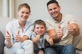 Portrait of happy family gesturing thumbs up while sitting on sofa at home - PhotoDune Item for Sale