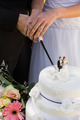 Extreme close-up mid section of a newlywed cutting wedding cake
