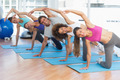 Full length portrait of sporty young people doing stretching exercises in fitness studio