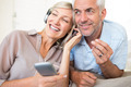 Cheerful mature man and woman with headphones and cellphone sitting on sofa at home - PhotoDune Item for Sale