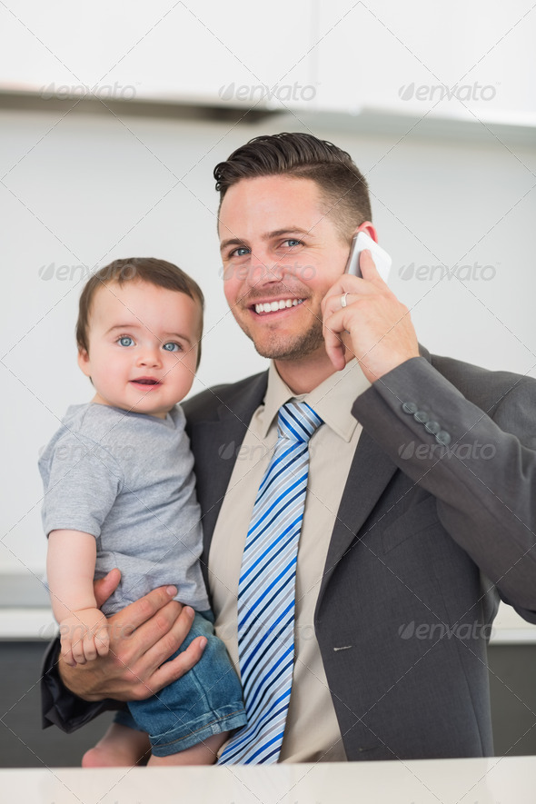 Portrait of happy businessman carrying baby boy while on call at home - Stock Photo - Images