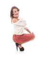Portrait Of Smiling Stylish Young Woman Crouching Over White Background - PhotoDune Item for Sale