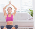 Fit blonde meditating in lotus pose with arms raised at home in the living room