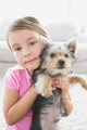 Little girl holding her yorkshire terrier puppy at home in the living room