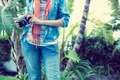 Woman wearing denim holding camera outside on a sunny day - PhotoDune Item for Sale