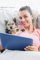 Attractive woman using tablet pc with her yorkshire terrier at home in the living room
