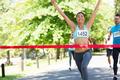 Female marathon winner with arms raised crossing finish line - PhotoDune Item for Sale