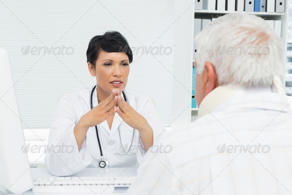 Young female doctor attentively listening to senior patient at the medical office - Stock Photo - Images