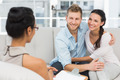 Smiling couple reconciling at therapy session in therapists office - PhotoDune Item for Sale