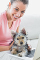 Cheerful woman using laptop with her yorkshire terrier at home in the living room