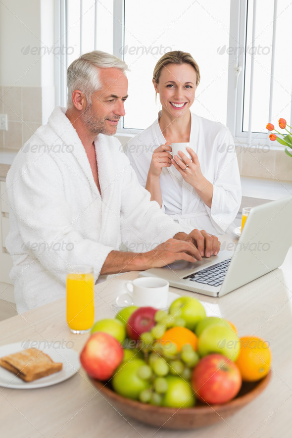 Smiling couple using laptop at breakfast in bathrobes at home in the kitchen - Stock Photo - Images