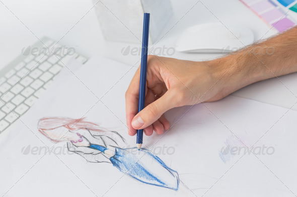 Extreme closeup of a fashion designer working on designs in the studio - Stock Photo - Images