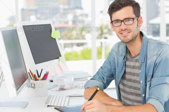Portrait of a casual male photo editor using graphics tablet in a bright office - Stock Photo - Images