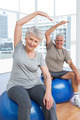 Happy senior couple doing stretching exercises on fitness balls in the medical office - PhotoDune Item for Sale