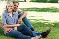Portrait of happy couple sitting together in a park