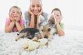 Siblings lying on rug looking at their yorkshire terrier with mother at home in the living room