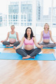 Meditating pregnant women in yoga class sitting in lotus position in a fitness studio