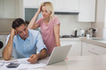 Unhappy couple with bills and laptop in the kitchen at home - PhotoDune Item for Sale